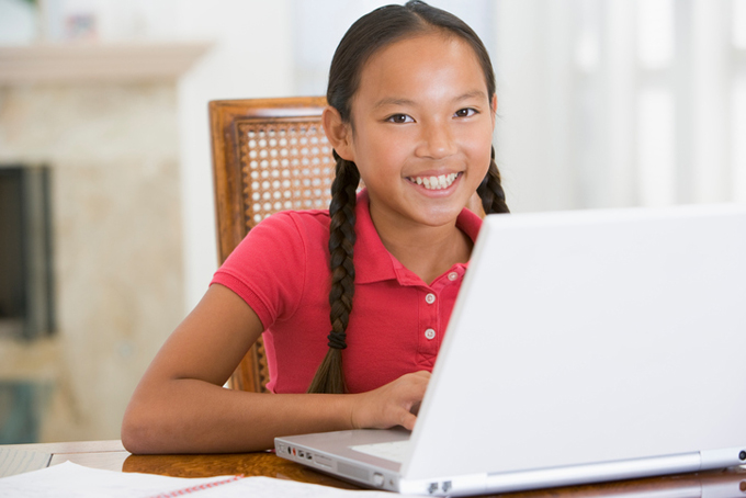 Smiling asian girl at computer