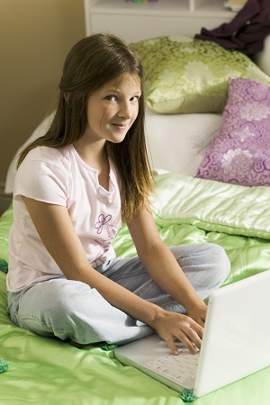 Girl sitting on bed on computer
