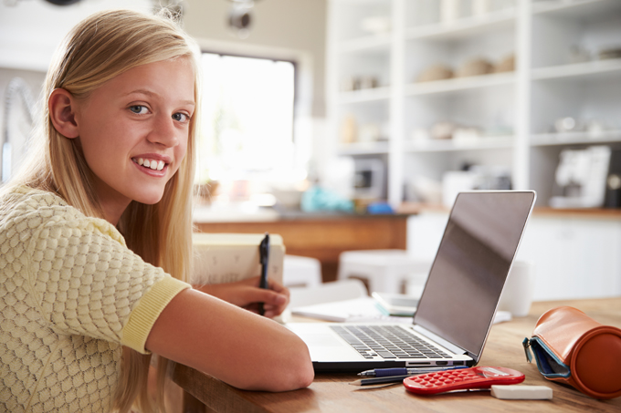 Smiling girl at table in front of laptop